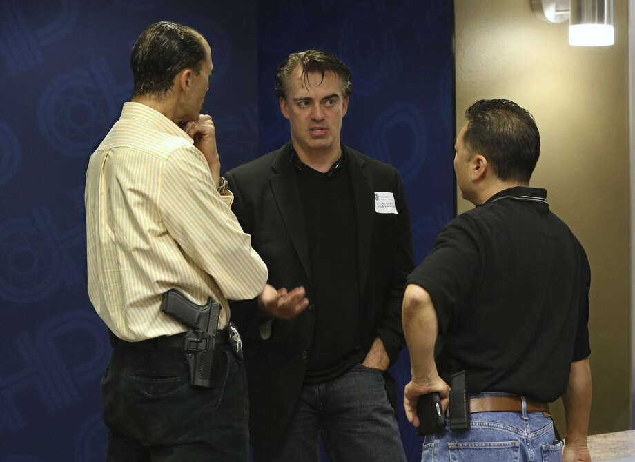 In this photo taken Thursday, Feb. 19, 2015, Rick Smith, chief executive officer and founder of Taser International, center, talks with Brant Garrick left, and Kenny Park of the Vallejo Police Department who attended the Taser tech summit at the California Highway Patrol Headquarters in Sacramento, Calif. Taser, the stun-gun maker, has become a leading supplier of body cameras for police and has cultivated financial ties to police chiefs whose departments have bought the recording devices. A review by The Associated Press shows Taser is covering airfare and hotel stays for police chiefs who travel to speak at marketing conferences. It is also hiring some recently retired chiefs as consultants, sometimes months after their cities signed contracts with Taser.(AP Photo/Rich Pedroncelli)