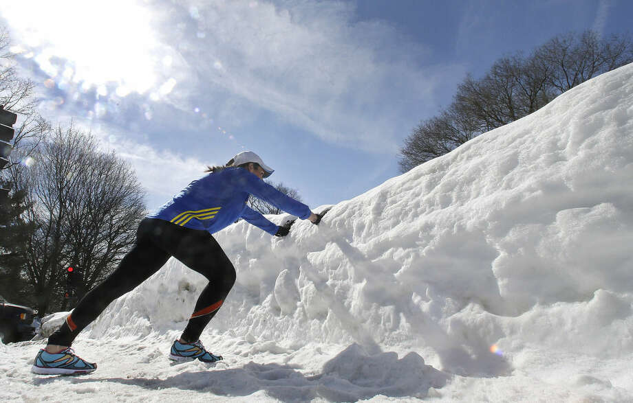 Runner Becca Pizzi, 34, uses a snowbank to stretch as she trains along Heartbreak Hill in Newton, Mass., Friday, Feb. 27, 2015. Running 26.2 miles requires endurance, but 8 feet of snow and lots of treacherous black ice are testing this year's participants in frustrating new ways. Though the worst of the winter now seems past, there are only 50 days left until April 20, the 119th running of the venerable race. (AP Photo/Elise Amendola)