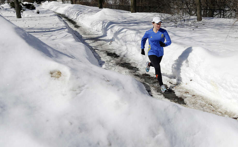 Runner Becca Pizzi, 34, trains along Heartbreak Hill in Newton, Mass., Friday, Feb. 27, 2015. Running 26.2 miles requires endurance, but 8 feet of snow and lots of treacherous black ice are testing this year's participants in frustrating new ways. Though the worst of the winter now seems past, there are only 50 days left until April 20, the 119th running of the venerable race. (AP Photo/Elise Amendola)