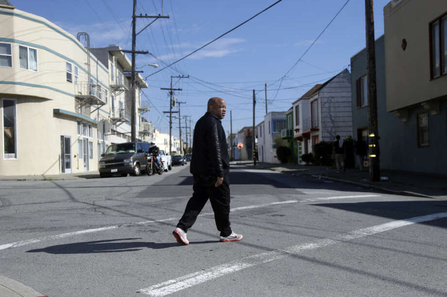 In this Thursday, Feb. 13, 2014 photo, Ernest Morgan walks around his neighborhood, in San Francisco. Morgan was released from San Quentin State Prison in 2011 after serving 24 years for the shotgun slaying of his stepsister as he burglarized his parents' home. Record numbers of murderers and other convicts serving life sentences with the possibility of parole are being freed from California's prisons as a result of key court rulings, new laws and efforts by officials to ease severe overcrowding at the state's correctional facilities. (AP Photo/Marcio Jose Sanchez)