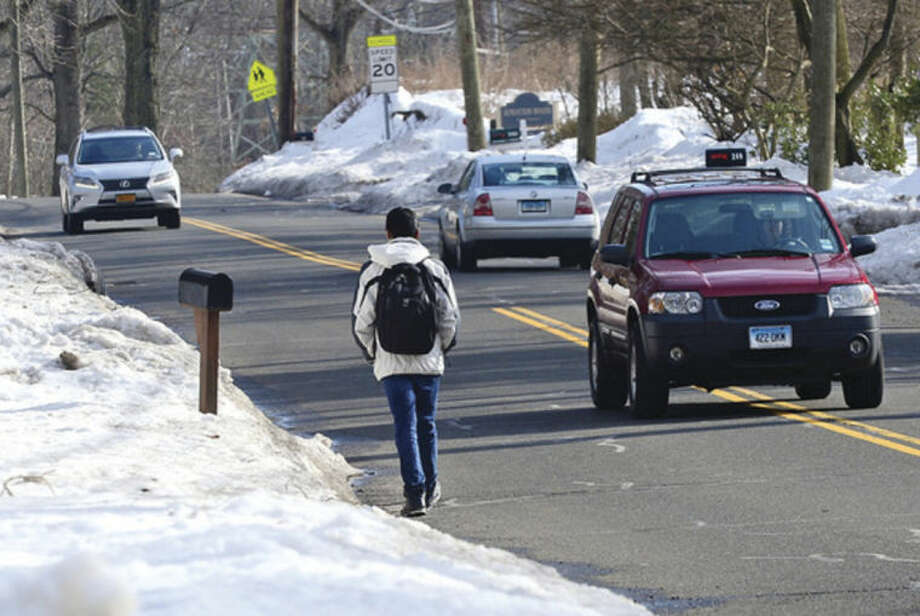 Hour photo / Erik TrautmannStudents who walk to school along Highland Avenue are forced to walk in the streets due to snow-filled sidewalks.