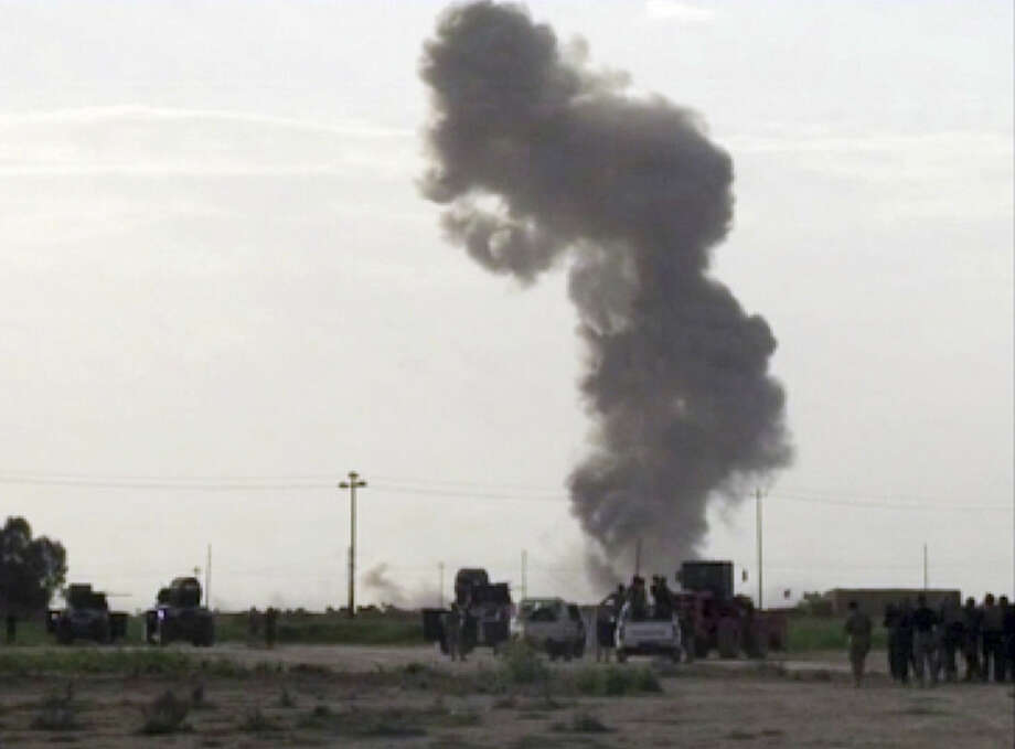 In this image made from video, smoke rises from an explosion as Iraqi forces, Shiite militiamen and Sunni tribal fighters battle Islamic State militants for control of Tikrit, Iraq, Tuesday, March 3, 2015. Backed by Shiite militias and Sunni tribal fighters as well as Iranian advisers, the government forces made little progress on the second day of a large-scale military operation to recapture Tikrit, which fell to the Islamic State group last summer, two local officials said. (AP Photo via AP video)