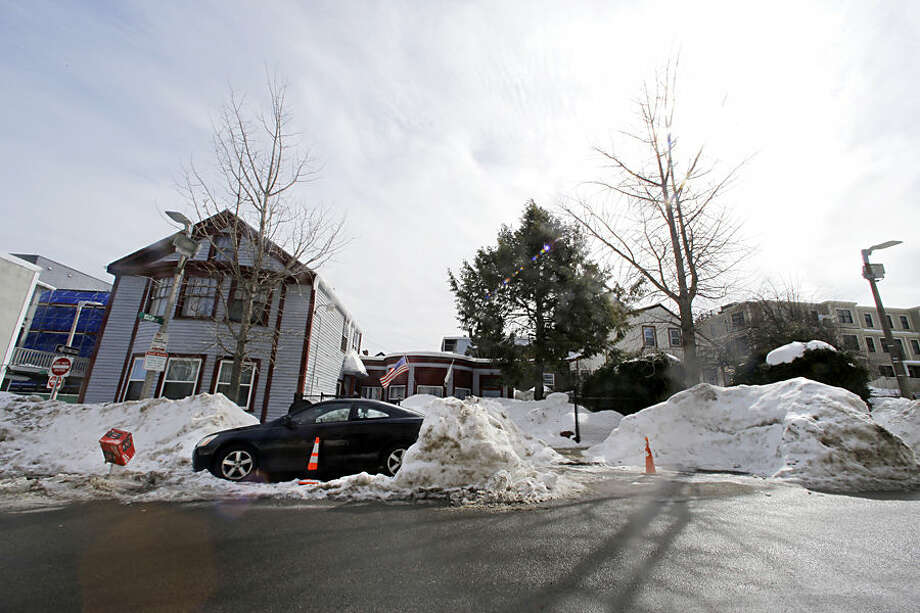 In this Feb. 23, 2015 photo, cones save parking spaces on a neighborhood street in South Boston. Officials typically turn a blind eye to the lawn chairs, orange cones and assorted bric-a-brac Bostonians use to reserve a parking space after clearing it of snow. That ends Monday, March 2, 2015, with an order from City Hall to remove space savers, reigniting the ugly parking wars that have pitted neighbor against neighbor. (AP Photo/Elise Amendola)