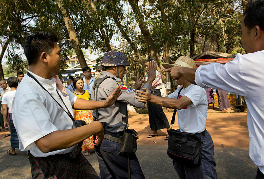Student protesters confront a police officer who tries to prevent them from traveling to join another group of students in a monastery, in Letpadan, north of Yangon, Myanmar, Monday, March 2, 2015. Truckloads of police prevented hundreds of students from marching onward to Myanmar's old capital Monday to protest a new law that they say will curb academic freedom. (AP Photo/Gemunu Amarasinghe)