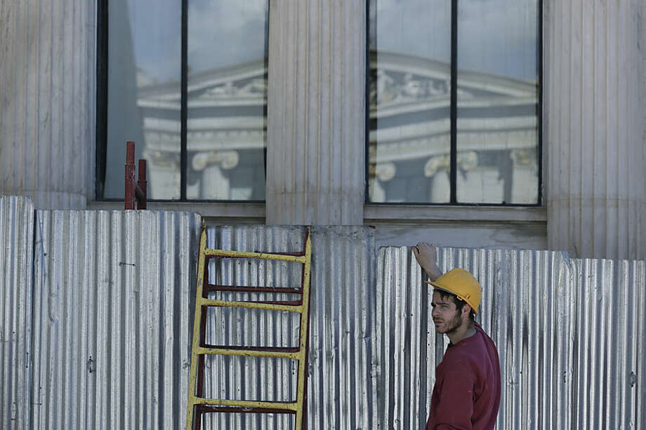 A worker stands beside metal sheeting on the 19th Century Athens Academy building, another section of which is reflected in the windows, in central Athens on Tuesday, March 3, 2015. Greece' appears headed to re-enter recession this quarter, after starting to expand again last year following a punishing six-year recession that led to record-high joblessness. Unemployment remains the highest in the European Union, hitting 25.8 percent in November. (AP Photo/Petros Giannakouris)
