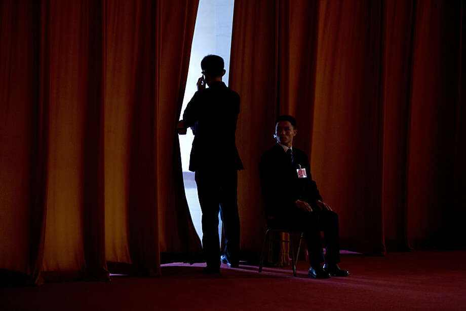 A plainclothes soldier watches the entrance to a curtained-off area during the the opening session of the Chinese People's Political Consultative Conference at the Great Hall of the People in Beijing Tuesday, March 3, 2015. The more than 2,000 members of China's top legislative advisory body convened their annual meeting Tuesday, kicking off a political high season that will continue with the opening of the national congress later in the week. (AP Photo/Mark Schiefelbein)