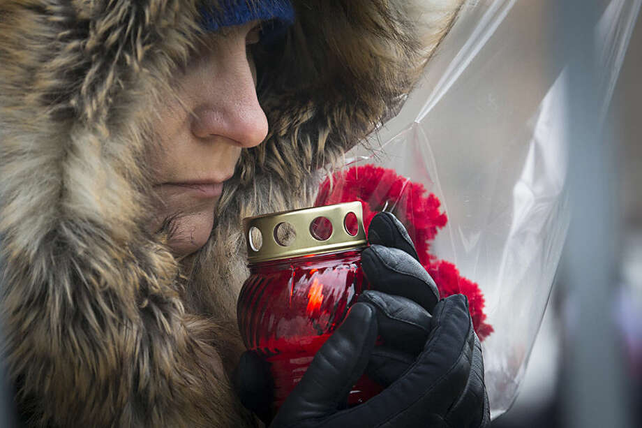 A woman holds a votive candle lining up to pay the last respects at the coffin of Boris Nemtsov during a farewell ceremony inside the Sakharov center in Moscow, Russia, Tuesday, March 3, 2015. Mourners are lining up outside a Moscow human rights center for the funeral of murdered Nemtsov. a charismatic Russian opposition leader and sharp critic of President Vladimir Putin, who was gunned down on Friday, Feb. 27, 2015 near the Kremlin. (AP Photo/Dmitry Lovetsky)