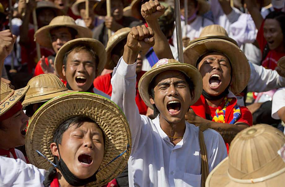 Student protesters wearing traditional Burmese hats shout slogans during a sit-in in Letpadan, north of Yangon, Myanmar, Tuesday, March 3. 2015. Hundreds of police have formed a human chain around student protesters staging a sit-in on a road Tuesday after being blocked from marching to Yangon, Myanmar's biggest city, to scrap a newly passed education law that they say curbs academic freedom. (AP Photo/Gemunu Amarasinghe)