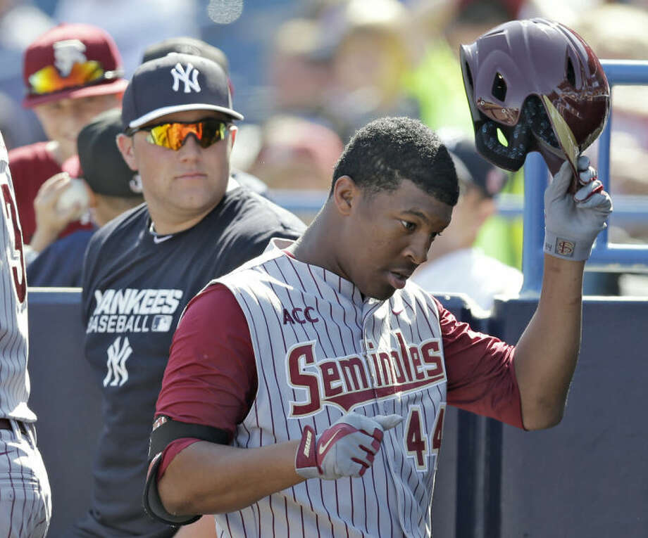 Florida State's Jameis Winston takes off his helmet after grounding out in the sixth inning during a spring training exhibition game against the New York Yankees Tuesday, Feb. 25, 2014, in Tampa, Fla. Winston is the 2013 Heisman Trophy winner. (AP Photo/Chris O'Meara)