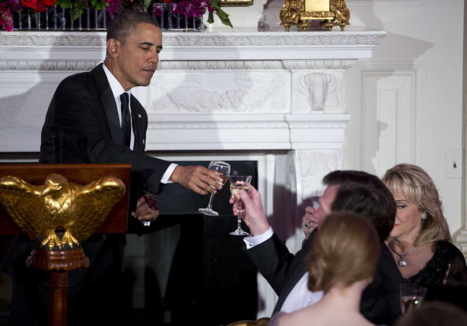 President Barack Obama toasts after delivering remarks during a dinner for the National Governors Association in the State Dining room of the White House on Sunday, Feb. 23, 2014, in Washington. (AP Photo/ Evan Vucci)