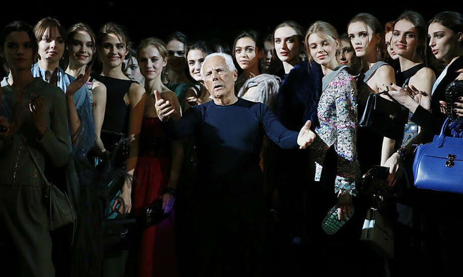 Italian fashion designer Giorgio Armani, center, poses with his models after presenting the Giorgio Armani women's Fall-Winter 2015-2016 collection, part of Milan Fashion Week, unveiled in Milan, Italy, Monday, March 2, 2015. (AP Photo/Luca Bruno)
