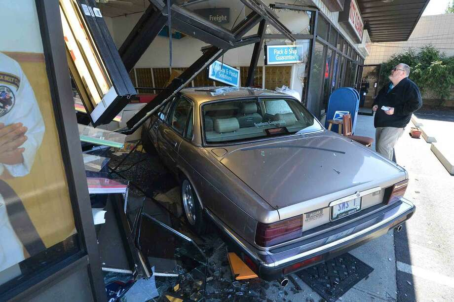 Hour Photo/Alex von Kleydorff Greg Bryson, Owner of The UPS Store at 304 Main ave. looks over the damage to his store after a Jaguar sedan crashed through the front window, the driver was transported by ambulance to Norwalk Hospital