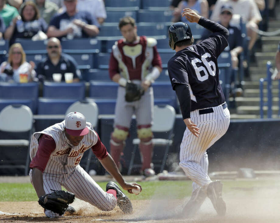 New York Yankees' John Ryan Murphy (66) scores past Florida State pitcher Brandon Johnson during the third inning of a spring training exhibition game Tuesday, Feb. 25, 2014, in Tampa, Fla. Murphy scored from third base on a pop out by teammate Gary Sanchez. (AP Photo/Chris O'Meara)