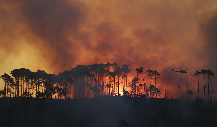In this photo taken Monday, March 2, 2015, a helicopter water bombs fire in the Tokai Forest near Cape Town, South Africa. A wildfire continues to burn across the city's southern peninsula Tuesday, March 3, 2015 after breaking out Sunday with firefighting re-enforcements being flown in to assist with battling the blaze (AP Photo/Mark Wessels)
