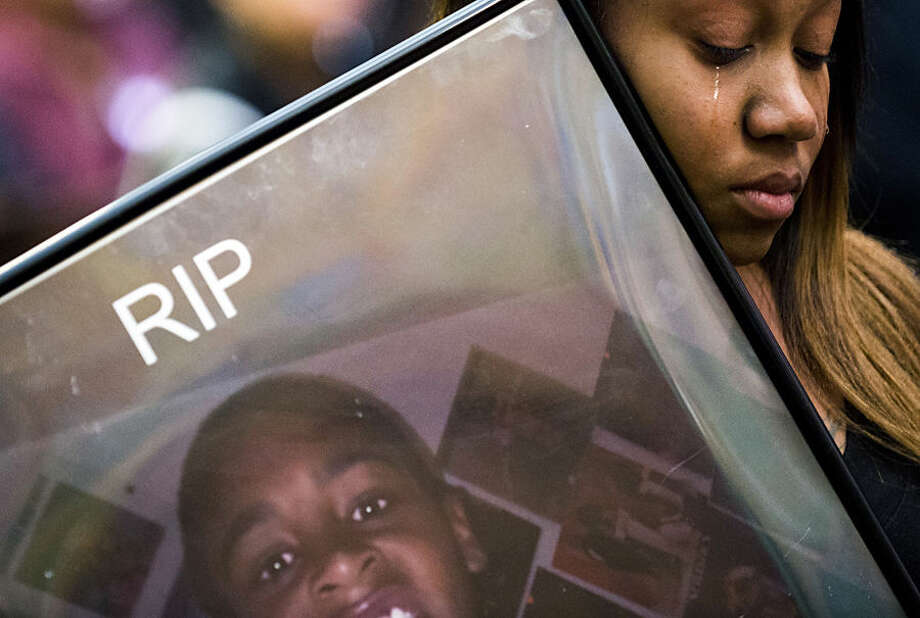 Andrea Washington holds a photo of her son Trashawn Macklin, who was killed in July 2013, while listening to Freeman Elementary teacher Laura Garrison speak about Macklin, Monday, March 2, 2015, in Flint, Mich., during the sentencing of Deonte Gray. Gray was convicted on three first-degree premeditated murder charges, including the death of Macklin, and sentenced to life in prison without parole. (AP Photo/The Flint Journal-MLive.com, Jake May)