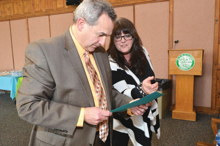 Hour Photo/Alex von Kleydorff City of Norwalk Purchasing Agent Gerald Foley reads a proclamation with Tax Collector Lisa Biagiarelli from Norwalk's delegation in the General Assembly in Hartford during a farwell party after more than 15 years of service to the city