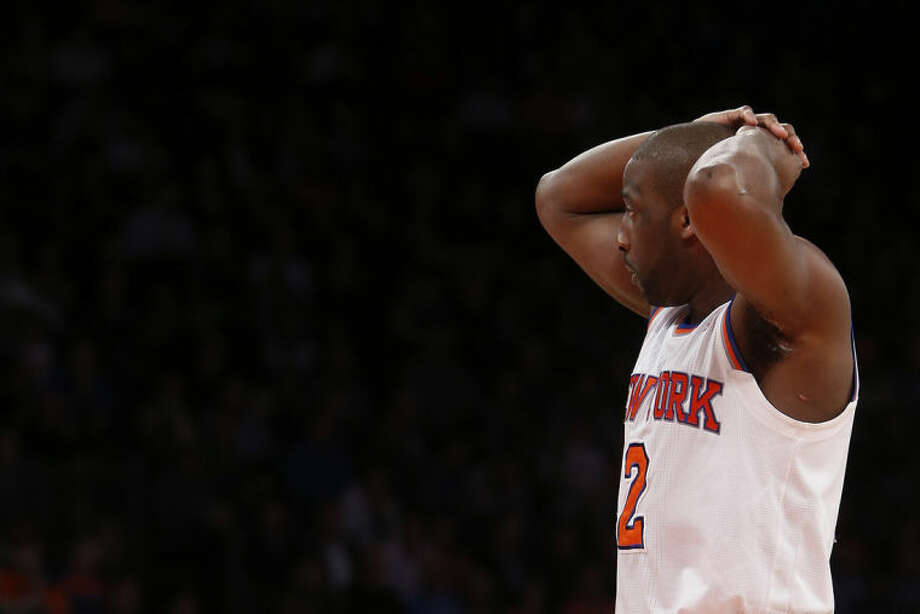 In this Monday, Feb. 24, 2014, photo, New York Knicks' Raymond Felton reacts during the second half of an NBA basketball game against the Dallas Mavericks in New York. Felton was arrested Tuesday on weapons charges after a lawyer for Felton's wife turned in a loaded gun allegedly belonging to the basketball star, saying she didn't want it in her home, police said. Felton turned himself in at 12:50 a.m. Tuesday, not long after the Knicks lost to the Mavericks. (AP Photo/Jason DeCrow)