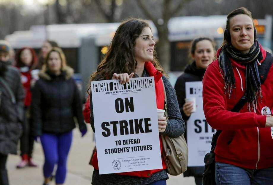 Colleen McDonough, a first-grade teacher at Walt Disney Magnet School in Chicago holds a picket sign outside the school, Friday, April 1, 2016, during a one-day strike by Chicago teachers and supporters aimed at halting education funding cuts. (AP Photo/Teresa Crawford)