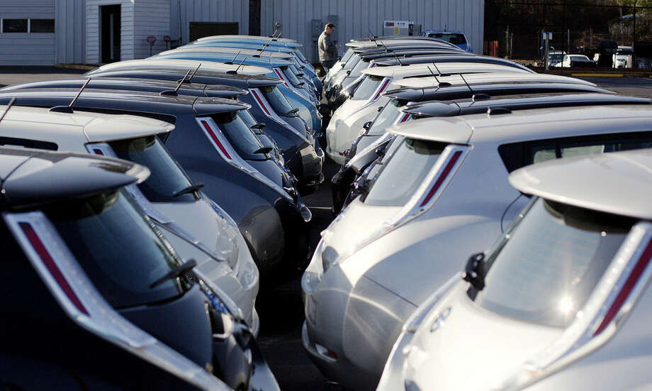 FILE - In this Feb. 5, 2015, file photo, Nissan electric vehicles sit on display at an auto dealership in Roswell, Ga. On Friday, April 1, 2016, major automakers report sales for March. (AP Photo/David Goldman, File)