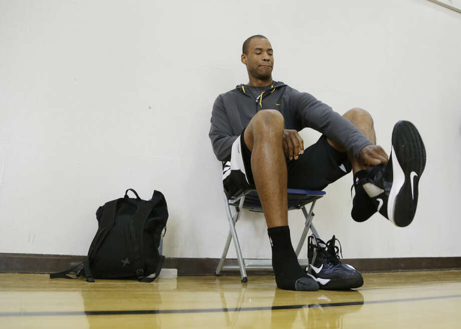 Brooklyn Nets center Jason Collins puts on his shoes before practice on the campus of UCLA in Los Angeles Tuesday, Feb. 25, 2014. Collins became the first openly gay athlete in North America's four major professional sports Sunday, Feb. 23, signing a 10-day contract with the Brooklyn Nets. (AP Photo/Reed Saxon)
