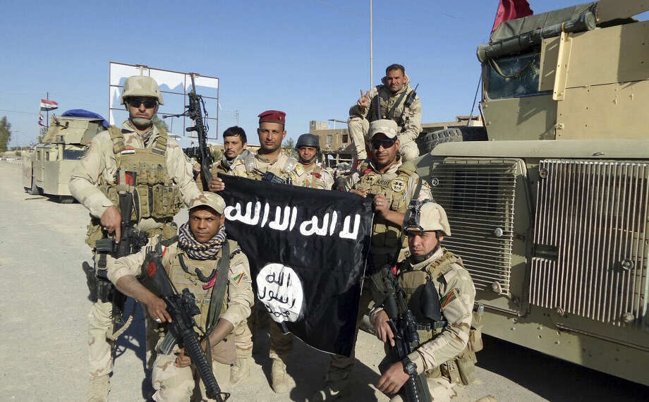 In this Wednesday, March 30, 2016 photo, Iraqi security forces celebrate as they hold a captured flag of the Islamic State group in the town of Kubaisa, Anbar province, west of Baghdad, Iraq. The trophy standard of the Islamic forces was captured after regaining control of Kubaisa. (AP Photo)
