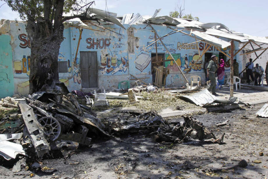Remains of a suicide car bomb strewn outside a restaurant, with the bodies of some of the victims laying near wall at centre, in Mogadishu, Somalia, Thursday, Feb. 27, 2014. A car bomb blast Thursday in a normally quiet Mogadishu neighborhood blew the facade off a tea shop where intelligence officers are known to congregate, killing at least 11 people, police said.( AP Photo/Farah Abdi Warsameh)