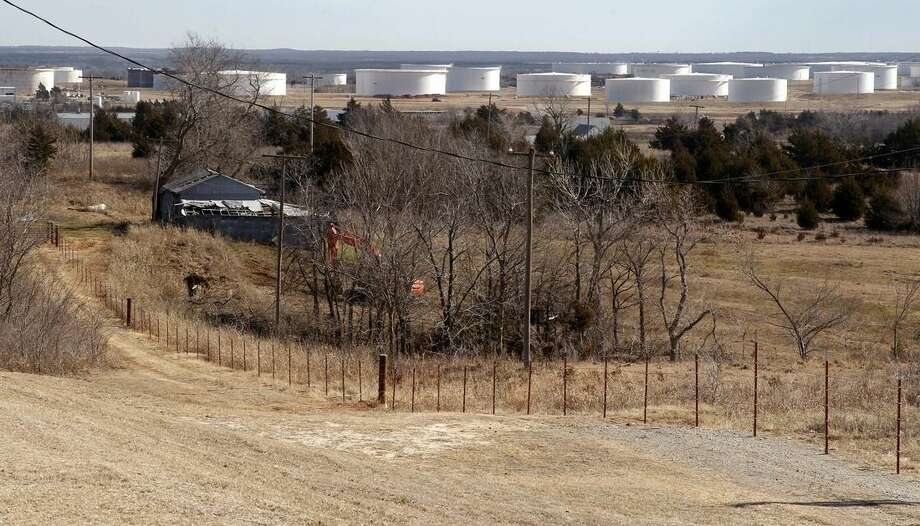 This Wednesday, Feb. 1, 2012 photo shows oil storage tanks on the edge of town in Cushing, Okla. For the past seven weeks, the United States has been producing and importing an average of 1 million more barrels of oil every day than it is consuming. That extra crude is flowing into storage tanks, especially at the country's main trading hub in Cushing, pushing U.S. supplies to their highest point in at least 80 years, the Energy Department reported Wednesday, Feb. 25, 2015. (AP Photo/Sue Ogrocki)