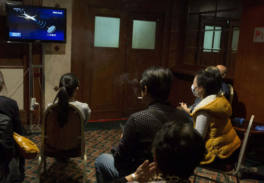 FILE - In this March 15, 2014, file photo, relatives of Chinese passengers aboard the missing Malaysia Airlines flight MH370 watch a news program about satellite tracking of the plane at a hotel in Beijing Saturday. Airlines and regulators have spent the past year since the disappearance of Flight MH370 debating how much flight tracking is necessary, balancing the economic costs against reassuring passengers another plane won't disappear. Now a plan is moving forward that would require airlines, by the end of 2016, to know their jets' positions every 15 minutes. (AP Photo/Ng Han Guan, Pool)