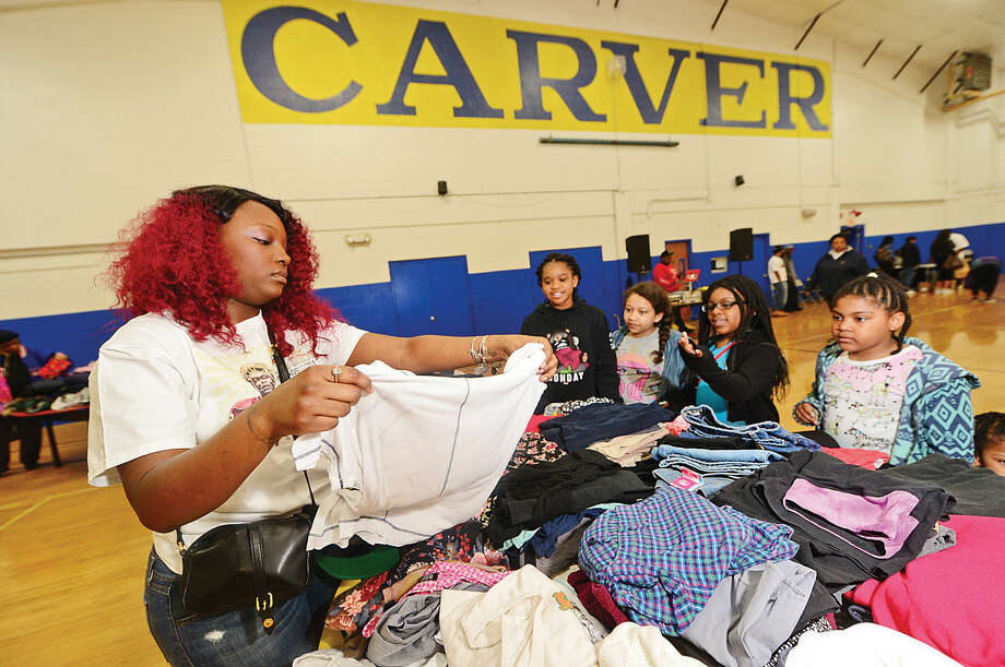 Hour photo / Erik Trautmann Volunteer Shikeda Paucar shows Janiya Dash, Trinady Cantey, Journee Dash and Toni Brown donated clothing during the Carver Clothing Drive heades by professional football player Silas redd Saturday at the Carver Community Center.