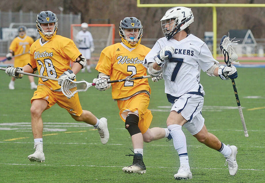 Hour photo / Erik Trautmann Staples High School Lacrosse player #7 Ross Goldberg gets by Weston's Andre DiPasquale and John Cannon during Staples rout Saturday.