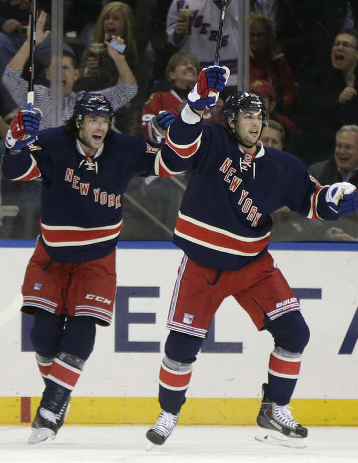 New York Rangers left wing Benoit Pouliot, left, celebrates with center Derick Brassard (16) after getting the assist on Brassard's first-period goal against the Chicago Blackhawks in an NHL hockey game at Madison Square Garden in New York, Thursday, Feb. 27, 2014. (AP Photo/Kathy Willens)