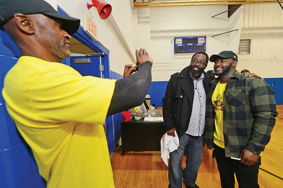 Hour photo / Erik Trautmann Former Norwalk resident and professional football player Silas Redd, right, and his former barber Jesse Holmes have their photo taken by Silas Redd Sr. as Redd heads up the Carver Clothing Drive Saturday at the Carver Community Center.