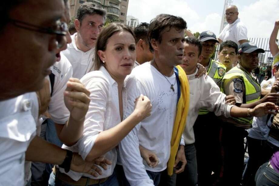FILE - In this Feb 18, 2014 file photo, Venezuelan congresswoman Maria Corina Machado, left, and opposition leader Leopoldo Lopez, center, are surrounded by anti-government demonstrators before Lopez surrenders to national guards, in Caracas, Venezuela. For many Venezuelans, the opposition's two highest profile leaders, former presidential candidate Henrique Capriles and the jailed Leopoldo Lopez, are still viewed as part of an elite detached from the working class life. (AP Photo/Juan Manuel Hernandez, File)