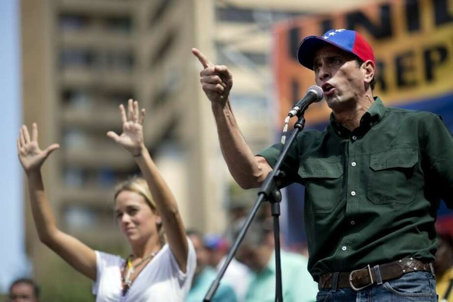 FILE - In this Feb 22, file photo, opposition leader Enrique Capriles delivers a speech next to Lilian Tintori, wife of detained opposition leader Leopoldo Lopez, during a rally in Caracas, Venezuel. Capriles says the opposition has put its differences over strategy behind them, adding that the government may have miscalculated its response to the protests as well. (AP Photo/Rodrigo Abd, File)