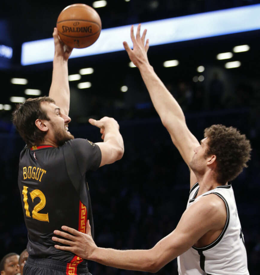 Golden State Warriors center Andrew Bogut (12) shoots over Brooklyn Nets center Brook Lopez in the first half of an NBA basketball game at the Barclays Center, Monday, March 2, 2015, in New York. (AP Photo/Kathy Willens)
