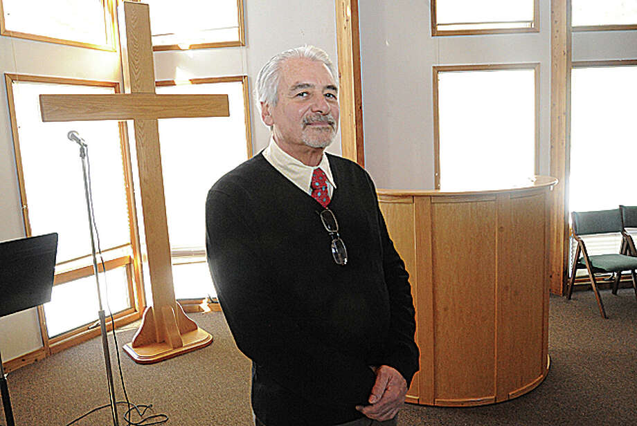 Pastor Peter Westfield stands in the sanctuary of his church, Crossroads Fellowship of Connecticut, which recently moved to Westport Road in Wilton.