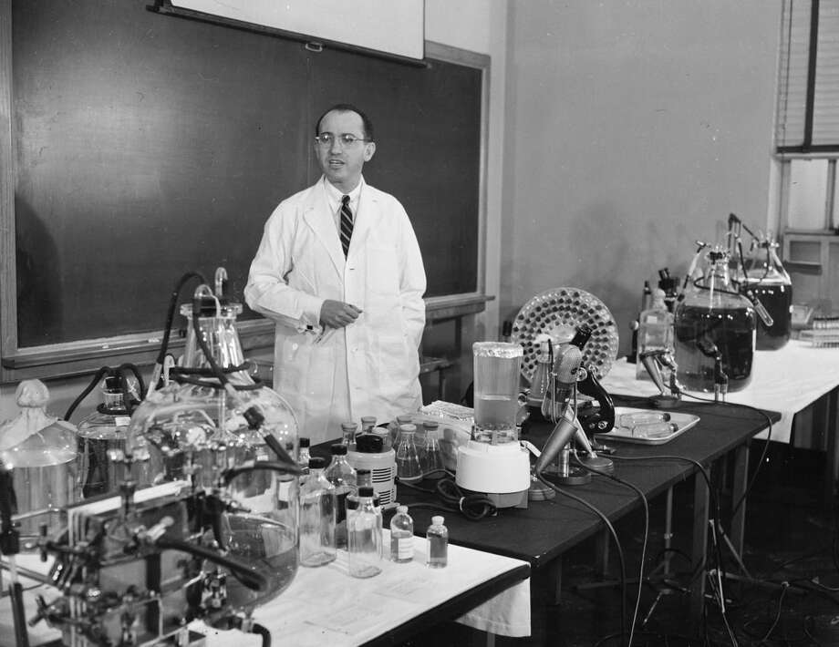 FILE - In this April 8, 1955 file photo, Dr. Jonas Salk, developer of the polio vaccine, describes how the vaccine is made and tested in his laboratory at the University of Pittsburgh. Around the beginning of the 20th century, vaccines were unregulated and could be as likely to harm a child as protect them. Opposition seemed to plummet for several decades, as vaccines got better and succeeded in beating back diseases that had long terrified families, including polio, measles and whooping cough. (AP Photo)