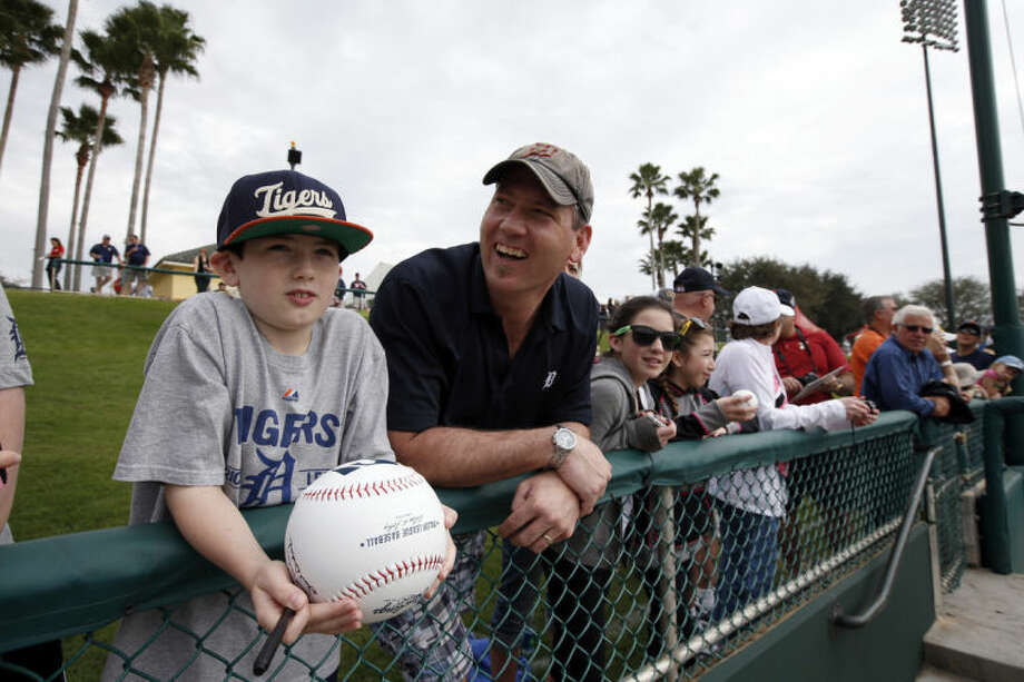 Gideon Kowalczyk, 10, and his father, John Kowalczyk, both from Bay City, Mich., wait for autographs before a spring exhibition baseball game between the Detroit Tigers and the Atlanta Braves, Wednesday, Feb. 26, 2014, in Kissimmee, Fla. After such a long, cold season, Americans across the winter-weary Midwest and the East Coast are desperate to escape to warm-weather destinations in California, Arizona and Florida. (AP Photo/Alex Brandon)