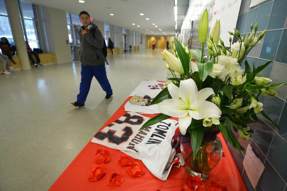 "Hour Photo/Alex von KleydorffFlowers and jerseys on a table in memoriam of Maurice ""Mo"" Tomlin Wednesday at Brien McMahon High School."