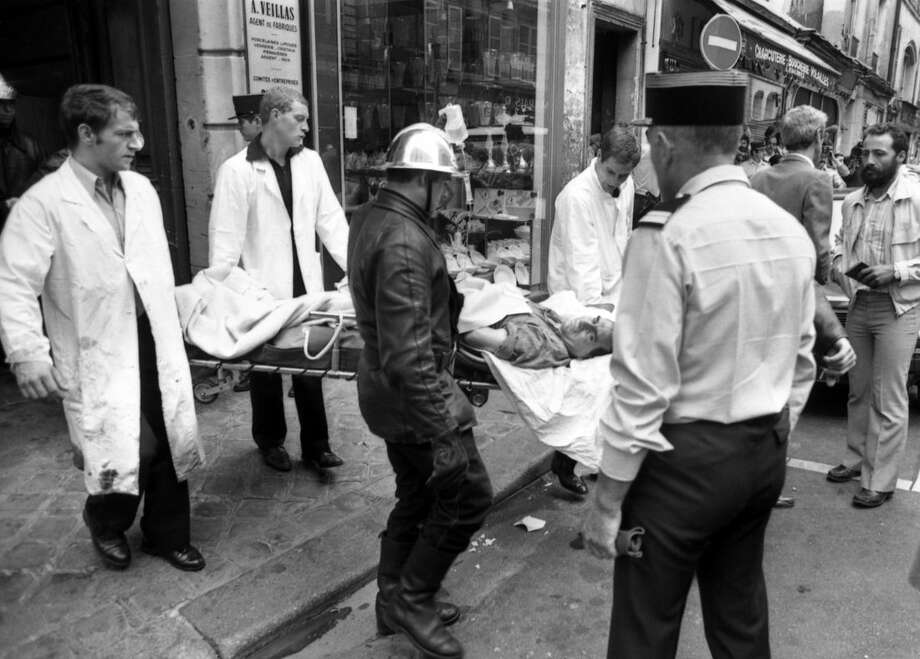 FILE - This Aug. 9, 1982, file photo shows a police officer looking at an injured man being carried away on a stretcher from the scene of a terror attack at Jewish restaurant and deli Jo Goldenberg in Paris, France. On Aug. 9, 1982, grenade-throwing Palestinians burst into Jo Goldenberg deli and sprayed machine-gun fire, killing six people _ including two Americans. Over 32 years after a deadly terror attack in Paris' old Jewish quarter, French authorities have finally identified three suspects and are seeking their arrest. (AP Photo/ Lionel Cironneau, File)