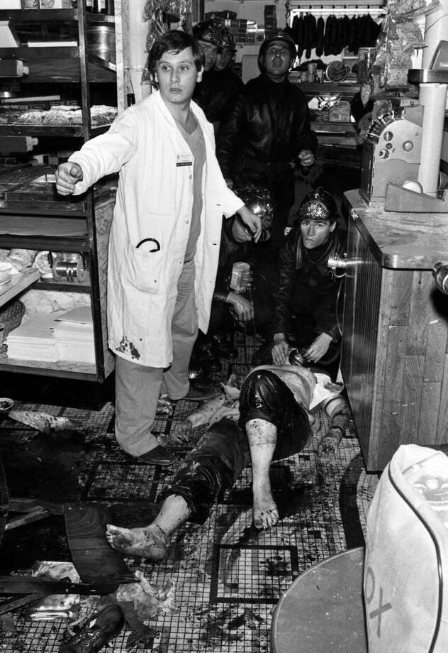 Editors Note: This image may contain nudity or graphic content. FILE - This Aug. 9, 1982, file photo shows firefighters and nurses tending to a casualty behind the bar at Jewish restaurant and deli, Jo Goldenberg, located on Rue des Rosiers in Paris, France, after the anti-Semitic terror attack by four armed men in the restaurant. More than 32 years after a deadly terror attack in Paris' old Jewish quarter, French authorities have identified three suspects and are seeking their arrest. On Aug. 9, 1982, grenade-throwing Palestinians burst into the Jo Goldenberg deli and sprayed machine-gun fire, killing six people — including two Americans. (AP Photo/ Aulnay, File)