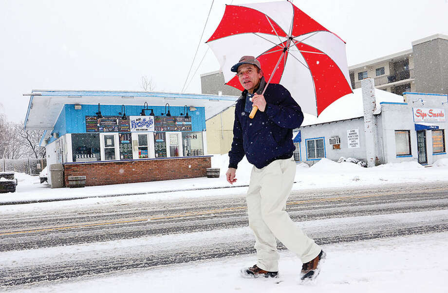 Hour photo / Erik Trautmann Local residents Younes Elhlibi deal with the most recent snowfall Thursday morning.