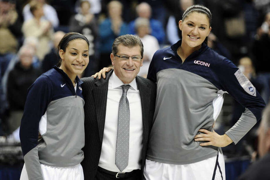 Connecticut's Bria Hartley, left, and Stefanie Dolson, right, stand with head coach Geno Auriemma, center, as they are honored at senior night before an NCAA college basketball game against Rutgers, Saturday, March 1, 2014, in Storrs, Conn. (AP Photo/Jessica Hill)