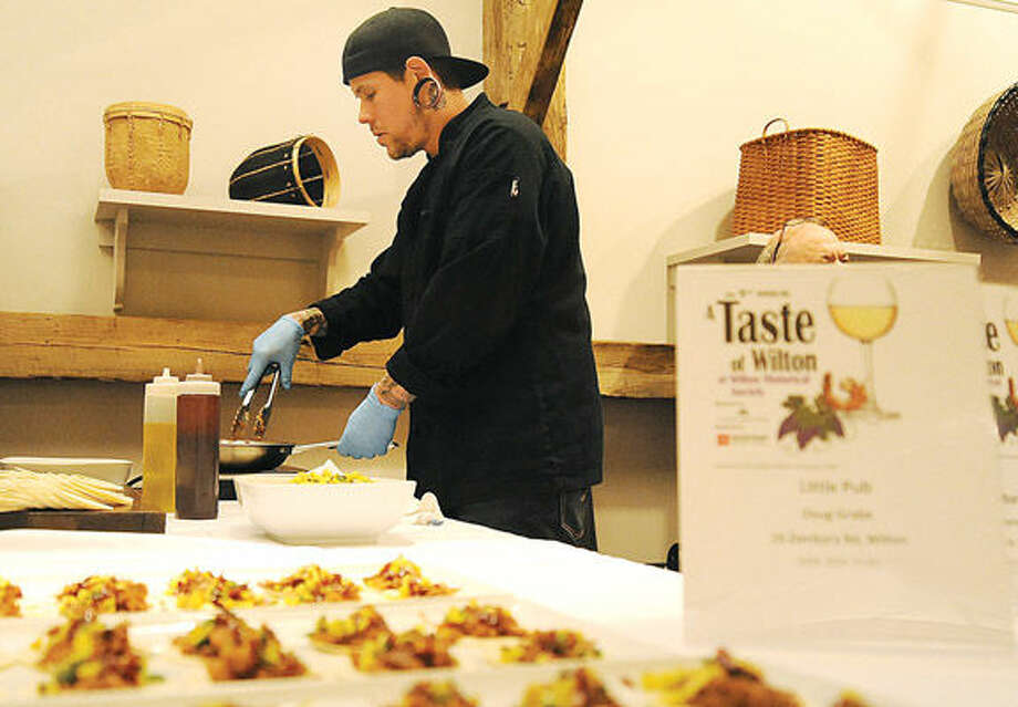 """Tim Passaro, Jr., executive chef at the Little Pub in Wilton, puts out appetizers Monday at """"A Taste of Wilton"""" held at the Wilton Historical Society."""