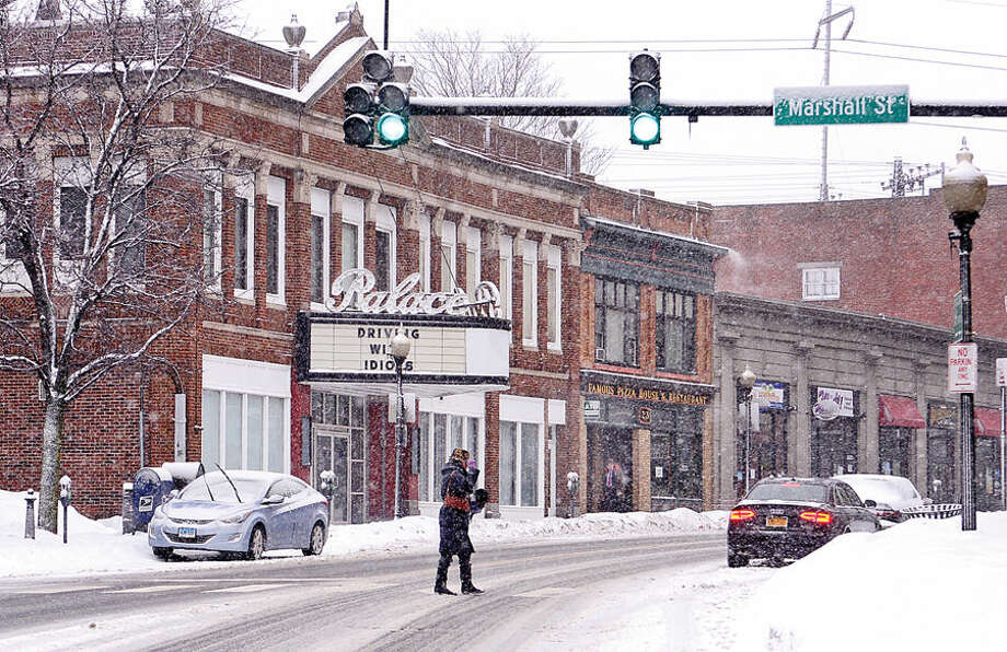 Hour photo / Erik Trautmann A woman shields pulls down her hat as she crosses North Main St during the most recent snowfall Thursday morning.