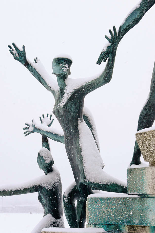 Hour photo / Erik Trautmann A statue in Veteran's Memorial Park accepts the snow as local residents deal with the most recent snowfall Thursday morning.