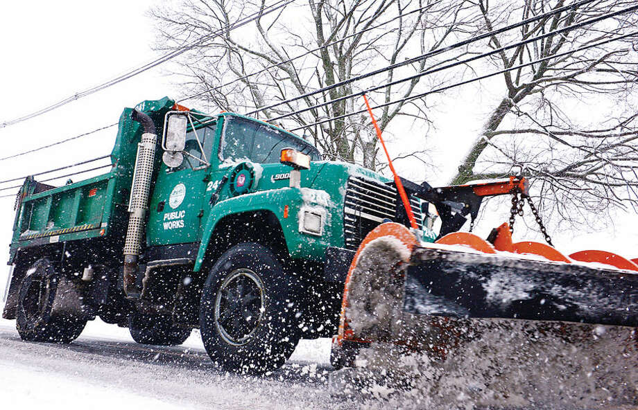 Hour photo / Erik Trautmann A Norwalk DPW truck plows alon Seaside Ave as local residents deal with the most recent snowfall Thursday morning.