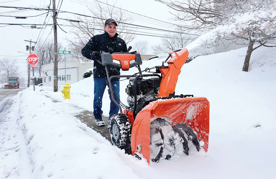 Hour photo / Erik Trautmann Local residents, including Norwalk Autocraft manager Ken Battis, deal with the most recent snowfall Thursday morning.