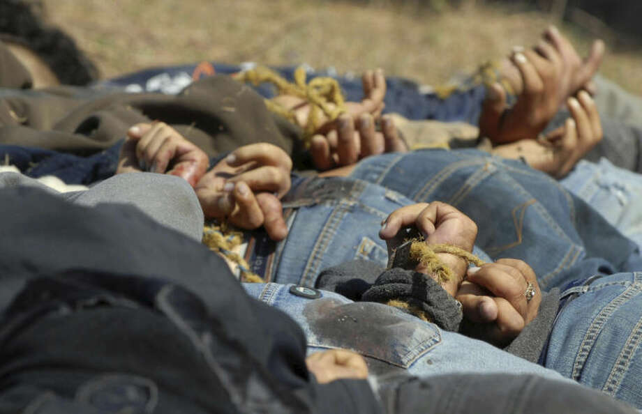 """FILE - In this Dec. 4, 2008, file photo, bodies from a total of 13 bullet-ridden men, with their hands tied behind their backs, victims of the drug war involving Joaquin """"El Chapo"""" Guzman's Sinaloa cartel, lie in a field near the town of San Ignacio in the pacific state of Sinaloa, Mexico. Guzman and his cohorts waged an increasingly bloody war over the year with rival gangs. (AP Photo/File)"""