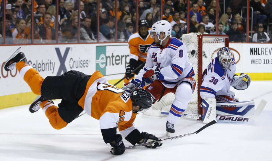 Philadelphia Flyers' Vincent Lecavalier (40) falls after trying to get a shot past New York Rangers' Kevin Klein (8) and Henrik Lundqvist (30) during the second period of an NHL hockey game, Saturday, March 1, 2014, in Philadelphia. (AP Photo/Matt Slocum)